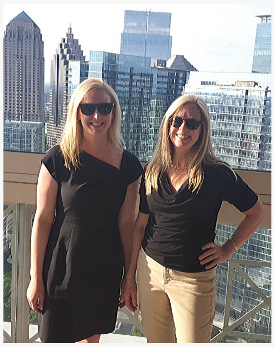 Equita Financial Network founders Katie Burke and Bridget Venus Grimes stand outside on city patio
